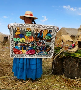 A Uros woman displays her embroidery depicting her family life.